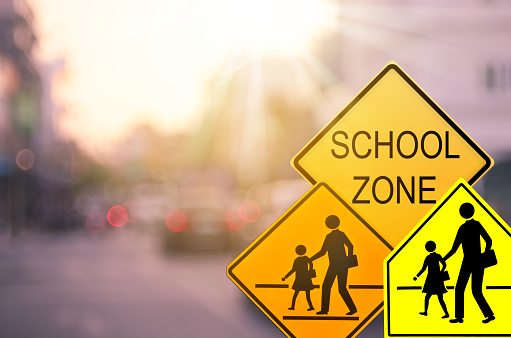 School zone warning sign on blur traffic road with colorful bokeh light abstract background. Copy space of transportation and travel concept. Vintage tone color style. 1157499287