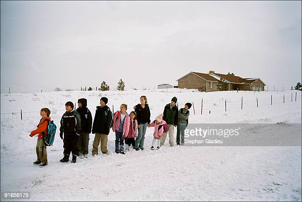 School-age children from a polygamist family consisting of one father, three mothers and 21 kids, wait for the school bus. This family lives in the...