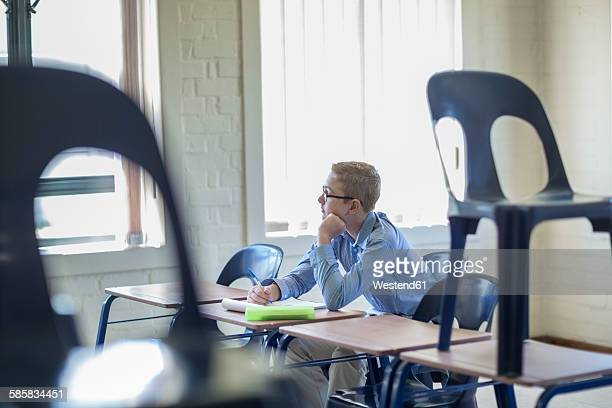 schoolboy alone in classroom - school detention stock pictures, royalty-free photos & images