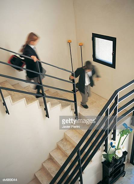 Schoolboy and a Schoolgirl Running Down Stairs