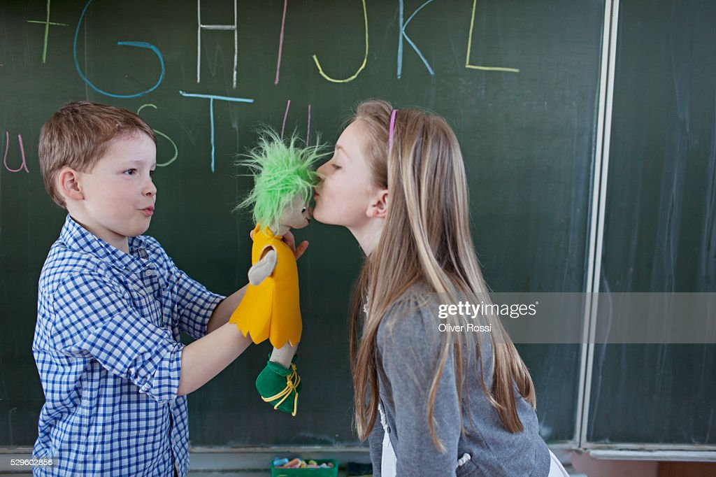 Schoolboy and girl (6-7) having fun in front of blackboard : Foto de stock