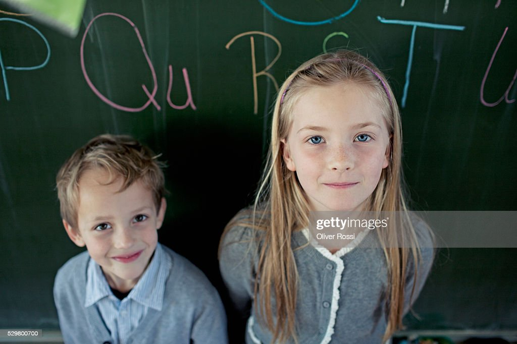 Schoolboy (6-7) and girl (8-9) posing in front of blackboard : Photo