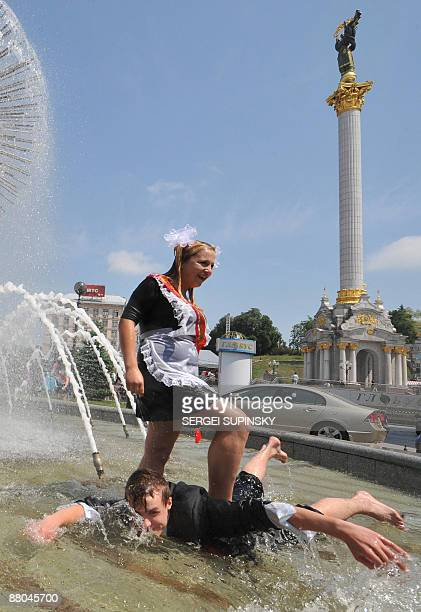 A schoolboy and schoolgirl frolic in a fountain during a traditional gathering of school graduates on Independence Square in Kiev on May 29 2009 Some...