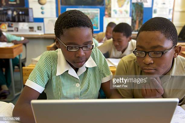 Schoolboy and schoolgirl work on a laptop computer in their classroom, KwaZulu Natal Province, South Africa