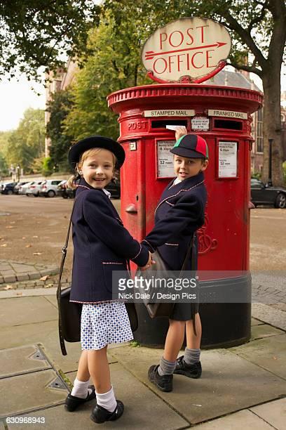 schoolboy and sister smiling while posting letter - girls with short skirts - fotografias e filmes do acervo