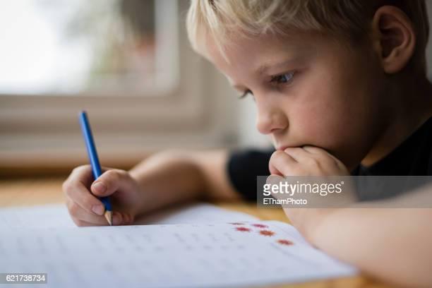 schoolboy at his desk doing his maths homework - konzentration stock-fotos und bilder