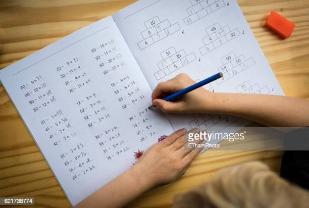 Schoolboy at his desk doing his maths homework
