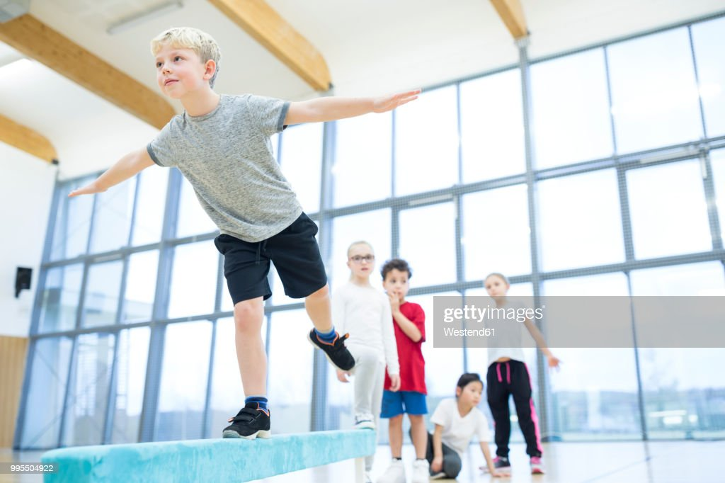 Schoolboy balancing on balance beam in gym class : Stock Photo
