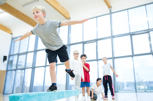 Schoolboy balancing on balance beam in gym class - gettyimageskorea