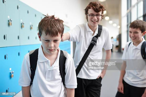 schoolboy being bullied in school corridor - bullying escolar fotografías e imágenes de stock