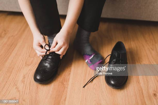 schoolboy boy is going to school, gets dressed, ties his shoelaces, puts on a briefcase - tying shoelace stock pictures, royalty-free photos & images
