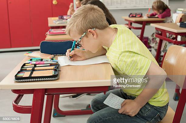 Schoolboy cheating on a test in classroom, Munich, Bavaria, Germany