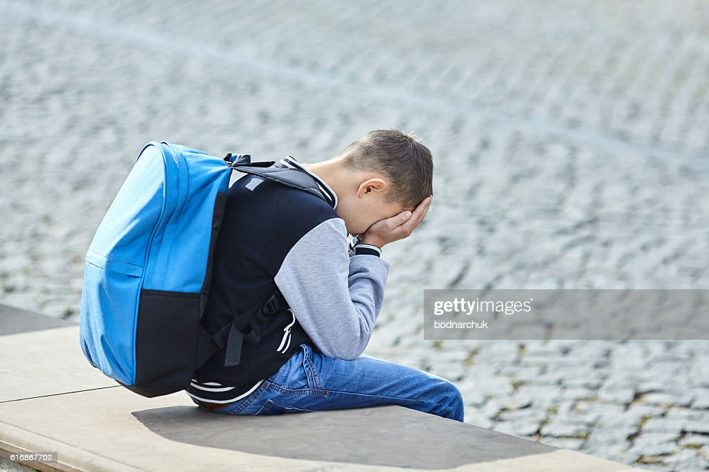 schoolboy crying on the street : Stock Photo