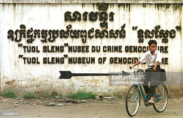 A schoolboy cycles past a sign for the Tuol Sleng genocide museum a former Phnom Penh highschool which the Khmer Rouge turned into an interrogation...