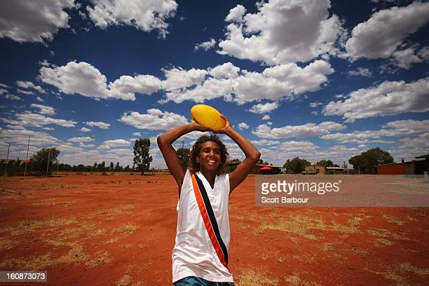 Schoolboy Deon Lechleitner catches an Australian Rules football as members of the Indigenous All Stars visit Yuendumu School in the Australian...