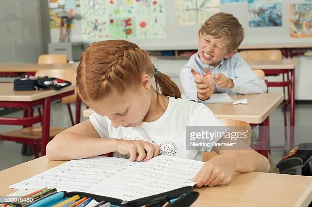 Schoolboy disturbing a schoolgirl with slingshot in classroom, Munich, Bavaria, Germany