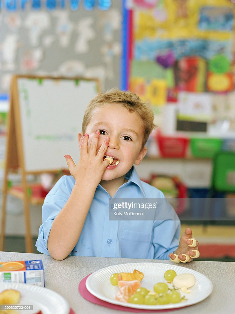 Schoolboy (4-6) eating at table, wearing crisps on fingers, portrait : Stock Photo