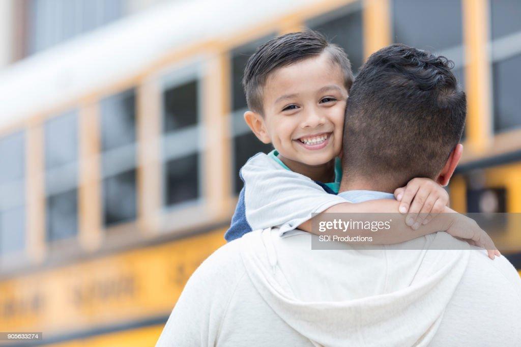 Schuljunge grüßt Vater nach dem ersten Tag : Stock-Foto