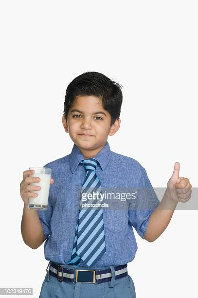 Schoolboy holding a glass of milk and gesturing thumbs up sign