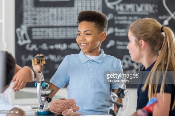 Schoolboy holds a specimen container in biology class