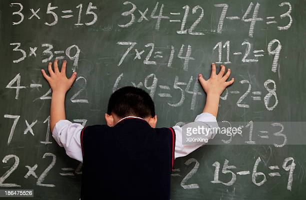 Schoolboy in front of blackboard with hands on chalkboard