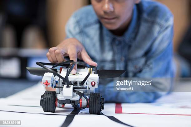 schoolboy in robotics class testing vehicle on test track - test track stock pictures, royalty-free photos & images