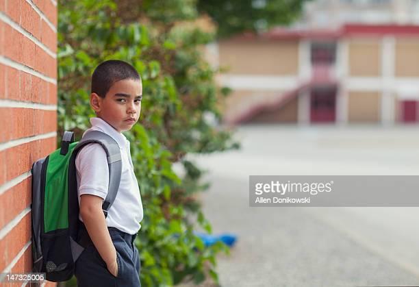 Schoolboy in uniform leaning against brick wall