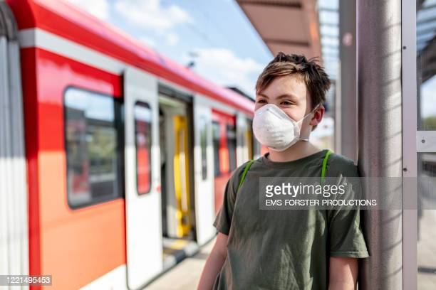 schoolboy is wearing a protective ffp-2 mask to prevent from corona virus while waiting at train station - respiratory disease stock pictures, royalty-free photos & images