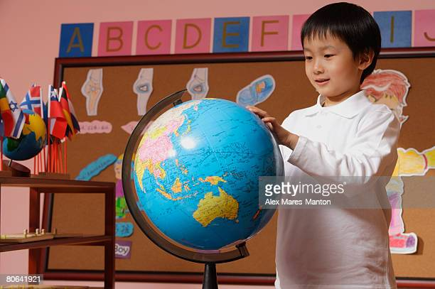 Schoolboy looking at globe