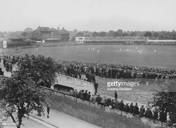 A schoolboy looks up from the street outside the ground as crowds of spectators in the grandstand and the Pavilion watch Bill Woodfull and Bill...