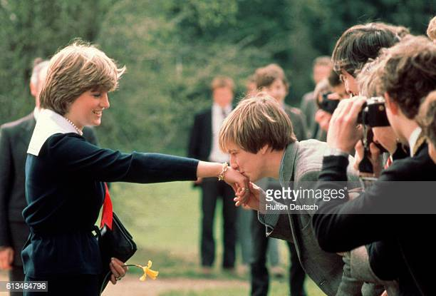 Schoolboy Nicholas Hardy kisses Lady Diana Spencer's hand after giving her a daffodil during her visit to Cheltenham