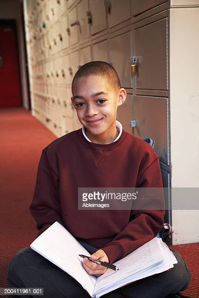 Schoolboy (8-10) on floor holding exercise book, smiling, portrait