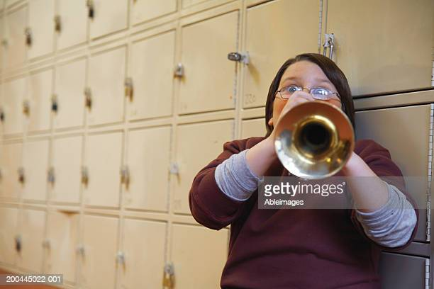 Schoolboy (8-10) playing trumpet, leaning against lockers, portrait