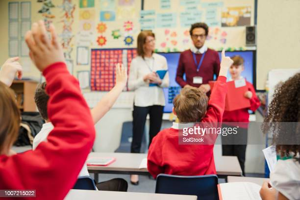 schoolboy presenting to his elementary class - classroom stock photos and pictures