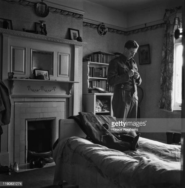 A schoolboy puts on his uniform as a member of the Home Guard during World War II UK March 1941