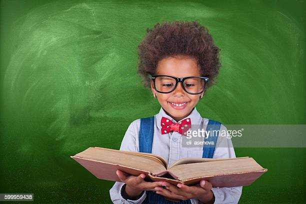 Schoolboy reading a book in front of school board