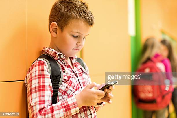 Schoolboy reading a text message on mobile phone.