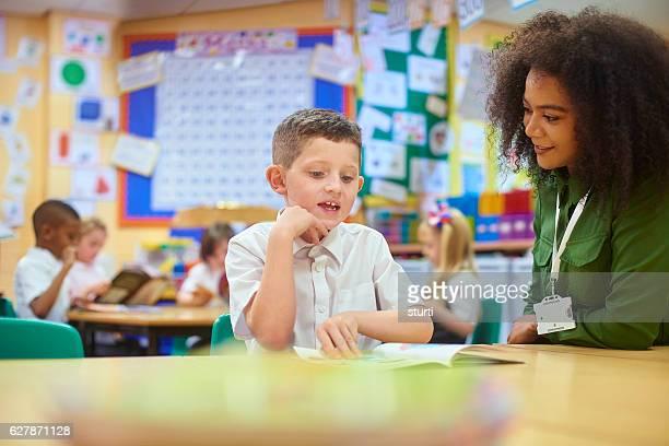 schoolboy reading to his teacher.