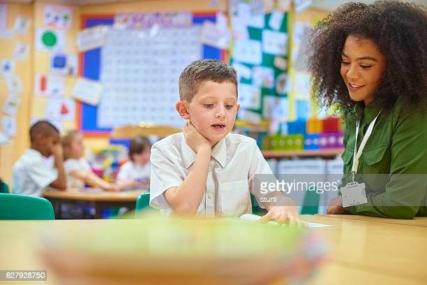 schoolboy reading to his teacher. - spelling stock pictures, royalty-free photos & images