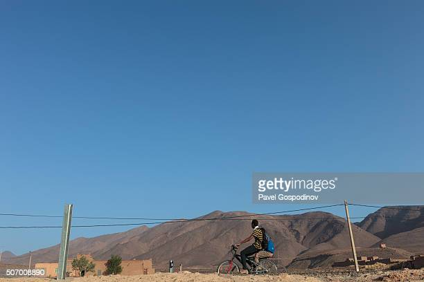 Schoolboy riding his bicycle to the local school in the Draa Valley, Morocco