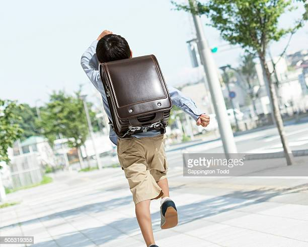 schoolboy running on street - children only stock pictures, royalty-free photos & images