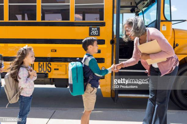 schoolboy shakes his new bus driver's hand - social grace stock pictures, royalty-free photos & images