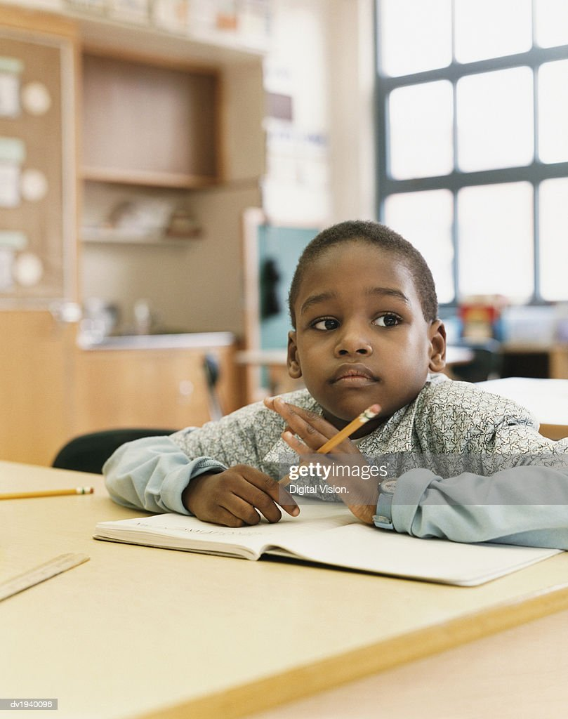 Schoolboy Sits at a Table Daydreaming : Stock Photo