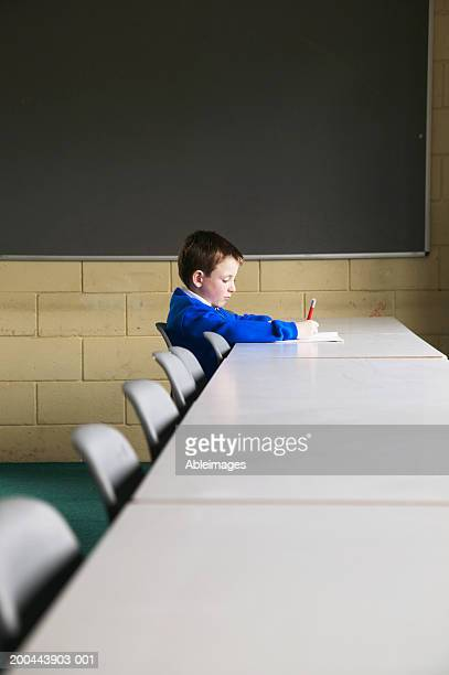 Schoolboy (5-7) sitting at classroom table, writing, side view