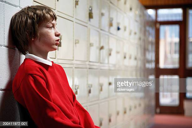 schoolboy (11-13) sitting in corridor leaning head on wall, side view - schoolboy stock pictures, royalty-free photos & images