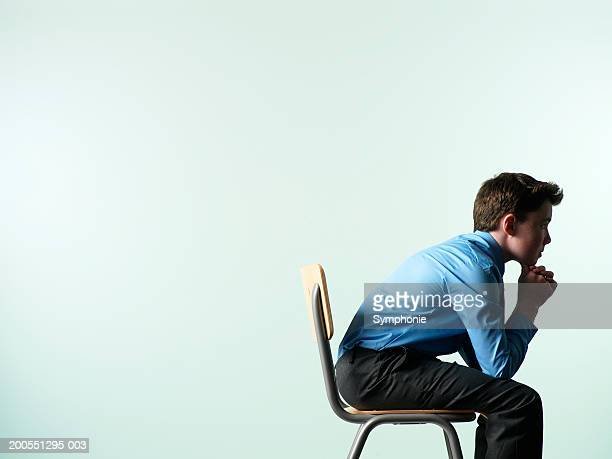 Schoolboy (12-13) sitting on chair, head in hand, side view