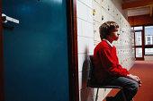 Schoolboy (11-13) sitting on chair in corridor, side view