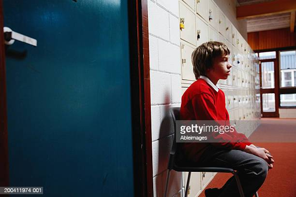 schoolboy (11-13) sitting on chair in corridor, side view - penalty stock pictures, royalty-free photos & images