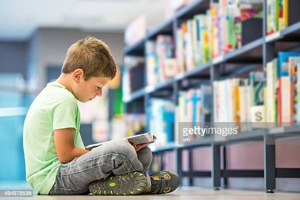 Schoolboy sitting on the floor in library