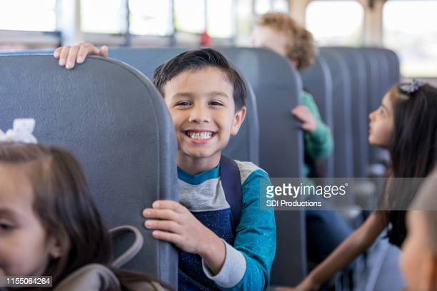 schoolboy smiles excitedly while sitting on school bus - anticipation stock pictures, royalty-free photos & images